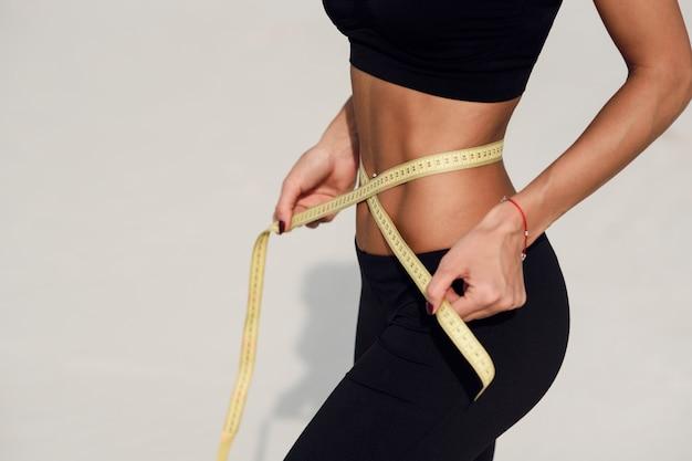 Concepto de alimentación saludable. chica joven con cintura perfecta con una cinta métrica en manos