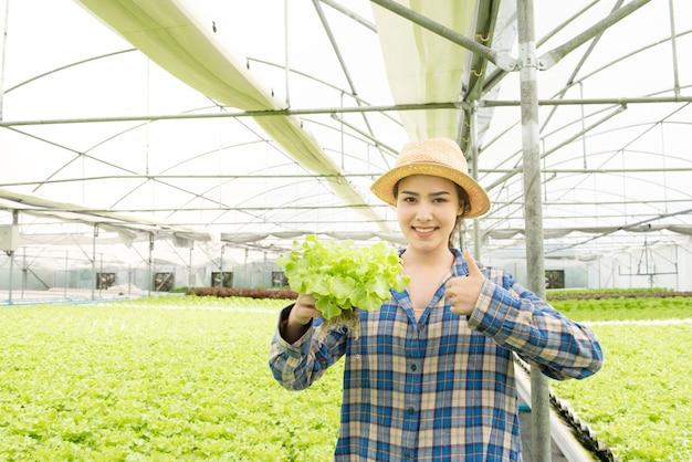 Concepto de alimentación saludable, dieta, comida vegetariana y personas - cerca de las manos asiáticas de la mujer joven que sostienen la espinaca
