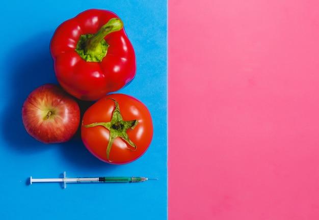 Concepto de alimentos genéticamente modificados sobre fondo rosa y azul