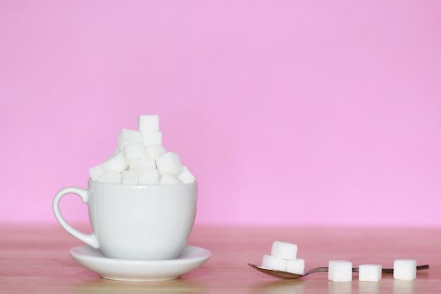 Concepto de alimentos poco saludables, azúcar blanco en una taza blanca sobre fondo rosa