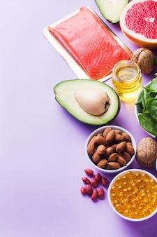 Concepto de alimentos saludables, productos antioxidantes: pescado y aguacate, nueces y aceite de pescado, pomelo sobre fondo rosa. copia espacio