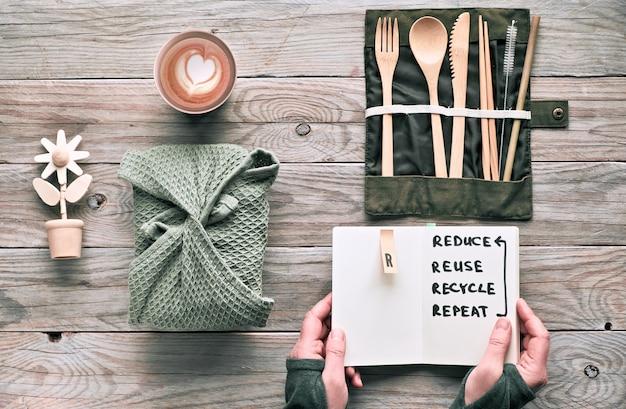 Concepto de almuerzo plano, cero desperdicio: cubiertos de madera reutilizables, fiambrera en textil, café en taza de café reutilizable. estilo de vida sostenible, manos sosteniendo la nota