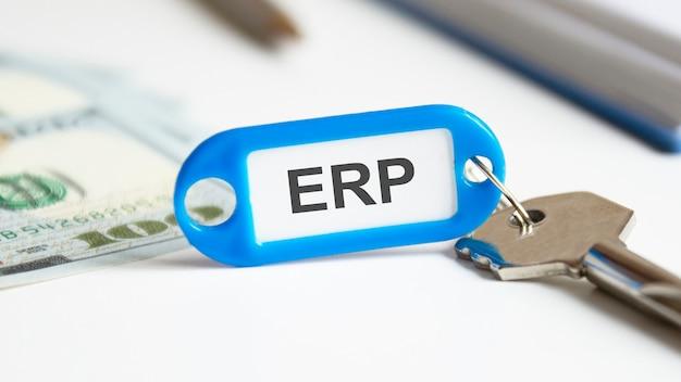 Concepto de alquiler de bienes raíces - clave con etiqueta erp. la llave está en el escritorio de la oficina. erp: abreviatura de planificación de recursos empresariales