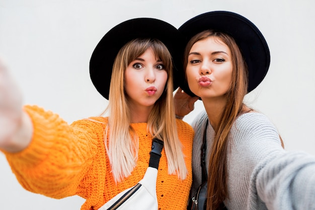 Concepto de amistad, felicidad y personas. dos muchachas sonrientes que susurran chismes en blanco