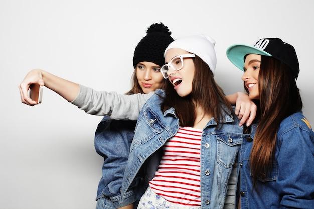 Concepto de amistad, personas y tecnología: tres adolescentes felices con smartphone tomando selfie