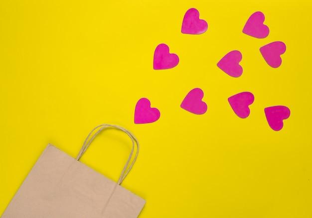 El concepto de amor a las compras. una bolsa de papel para ir de compras y un montón de corazones decorativos sobre un fondo amarillo. día de san valentín. vista superior.