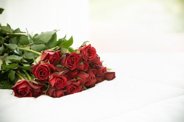 Concepto de amor y día de san valentín. cerca del ramo de rosas rojas en cama blanca