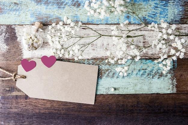 Concepto de amor de etiqueta de papel marrón en blanco con corazón y flores en madera vieja