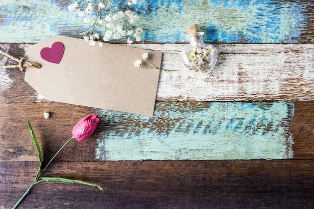 Concepto de amor de etiqueta de papel marrón en blanco con corazón rojo y flores en madera vieja