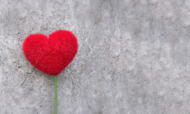 Concepto de amor: forma de corazón rojo sobre cemento