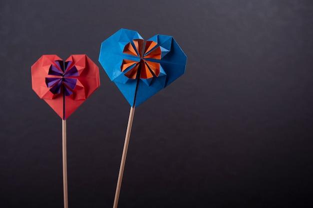 Concepto de amor par de origami de papercraft hecho a mano corazones de papel de colores tiro de primer plano en el estudio