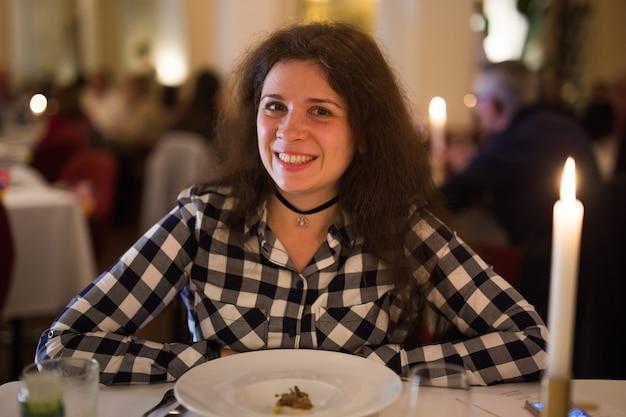 Concepto de amor, relación y fecha - mujer joven feliz a la luz de las velas durante una cena romántica en el restaurante.