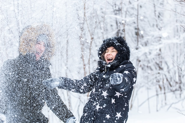 Concepto de amor, relación, temporada y amistad - hombre y mujer divirtiéndose y jugando con nieve en el bosque de invierno