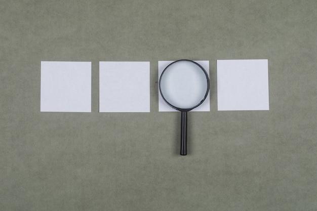 Concepto de análisis empresarial con notas adhesivas, lupa sobre superficie plana gris endecha.