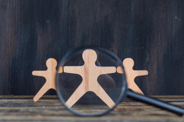 Concepto de análisis de marketing con lupa sobre figura de madera en primer plano de fondo de madera y grunge.