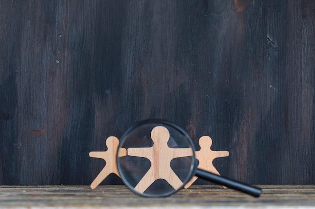 Concepto de análisis de marketing con lupa sobre figura de madera en vista lateral de fondo de madera y grunge.