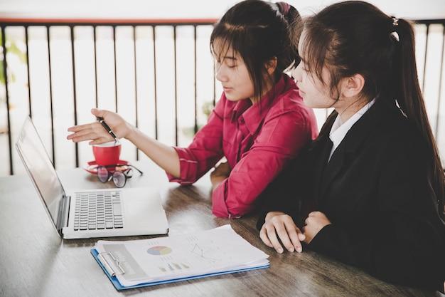Concepto de análisis de negocio. empresaria que analiza documentos de negocios, informe financiero, trabajando en la computadora portátil, teléfono inteligente móvil en el escritorio de oficina, de cerca.