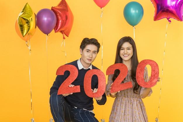 Concepto de año nuevo 2020. retrato de hombre guapo y sonriente hermosa joven asiática con papel número rojo y fiesta de globo colorido