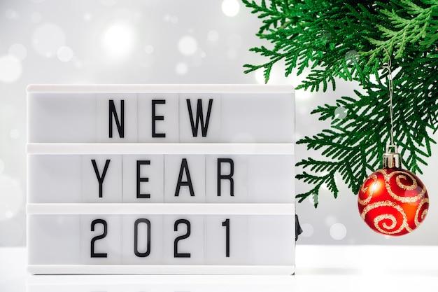 Concepto de año nuevo 2021, árbol de navidad y texto sobre fondo blanco.