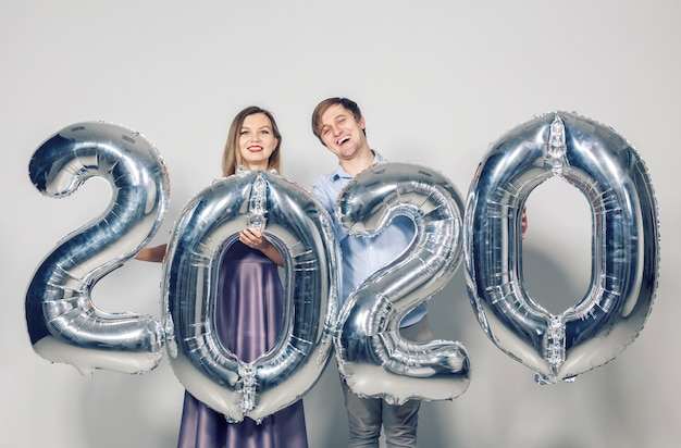 Concepto de año nuevo, celebración y vacaciones: amor pareja divirtiéndose con signo 2020 hecho de globos plateados para año nuevo