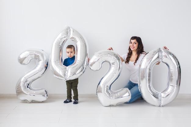 Concepto de año nuevo, celebración y vacaciones: madre e hijo sentados cerca del letrero 2020 hecho de globos plateados para año nuevo en sala blanca