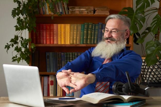Concepto de aprendizaje a distancia. el maestro satisfecho se estira después del final de la lección en línea y sonríe, enfoque selectivo