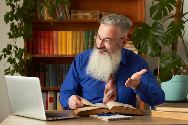 Concepto de aprendizaje a distancia. profesor profesor tutor enseña disciplina en línea. hombre barbudo maduro responde a la pregunta del profesor a través de la computadora portátil.