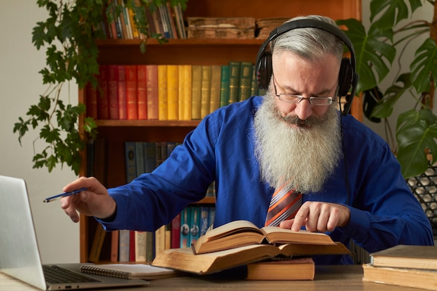 Concepto de aprendizaje a distancia. profesor profesor tutor enseña disciplina en línea. hombre barbudo maduro responde a la pregunta del profesor a través del portátil.