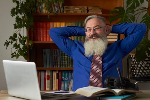Concepto de aprendizaje a distancia. profesor satisfecho mirando portátil con las manos detrás de la cabeza y sonrisas, enfoque selectivo