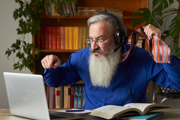 Concepto de aprendizaje a distancia. profesor tutor frenético se mete en la computadora portátil y se cuelga de la corbata, enfoque selectivo