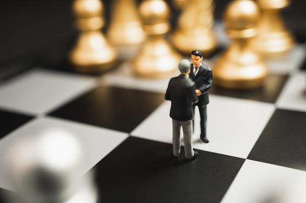 Concepto de apretón de manos de asociación empresarial en miniatura. apretón de manos de hombres de negocios exitosos después de un buen trato en ajedrez de oro y plata