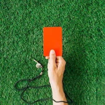 Concepto de árbitro con mano sujetando tarjeta roja