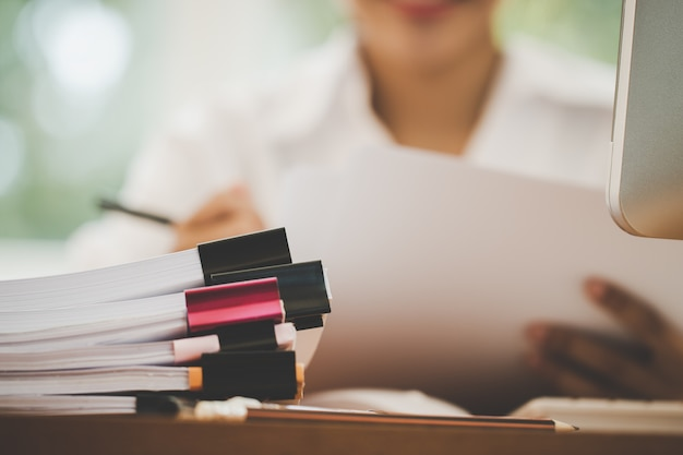 Concepto de archivo de informe de presupuesto de planificación contable: cheque de oficinas de mujer de negocios trabajando para organizar