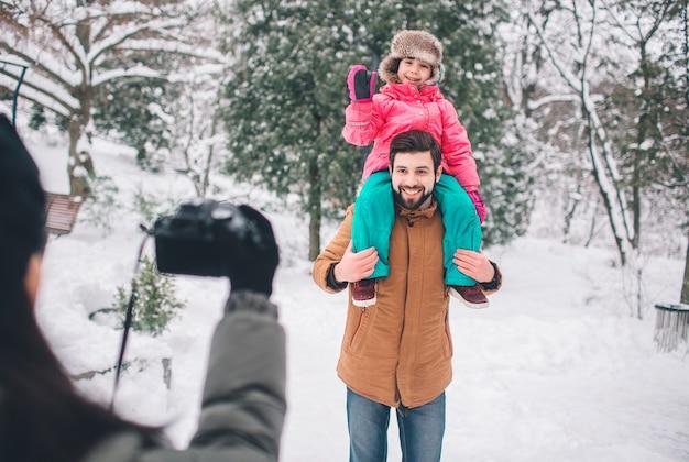 Concepto de arenthood, de la moda, de la estación y de la gente - la familia feliz con el niño en invierno viste al aire libre. tomar fotos entre ellos