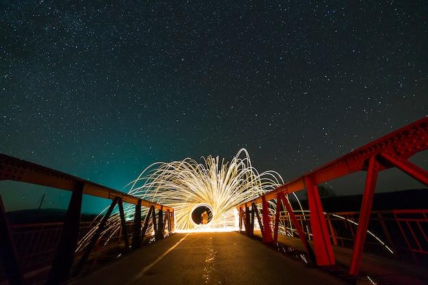 Concepto de arte de pintura ligera. disparo de larga exposición de lana de acero giratoria en círculo abstracto haciendo duchas de fuegos artificiales de brillantes destellos amarillos brillantes en un largo puente sobre el cielo estrellado de la noche azul