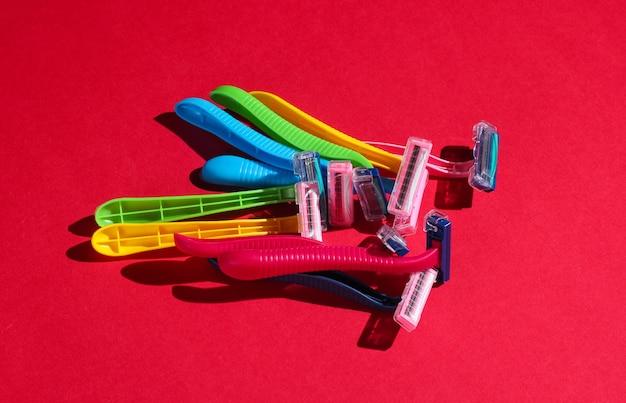 Concepto de arte pop de belleza y moda. muchas maquinillas de afeitar de plástico de colores en rojo.