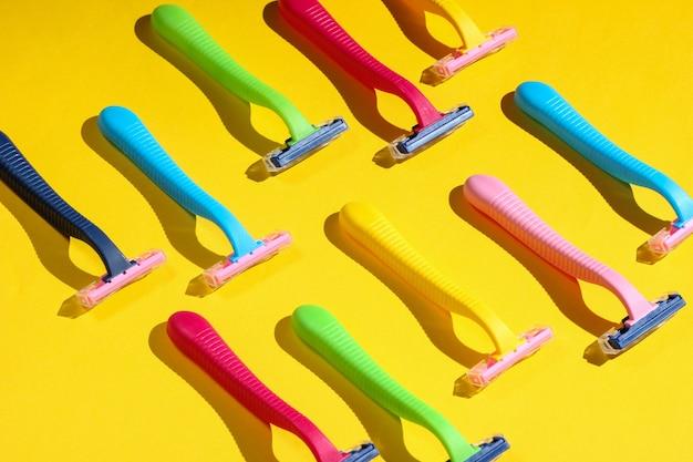 Concepto de arte pop de belleza y moda. muchas navajas de plástico de colores en amarillo.