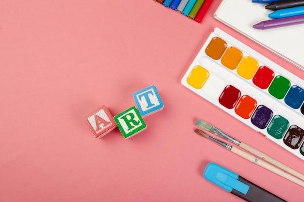 Concepto de arte. útiles escolares y cubos alfabéticos de madera.