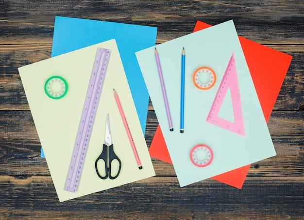 Concepto de artesanía con papeles, reglas, tijeras, lápices, cintas sobre fondo de madera plana.