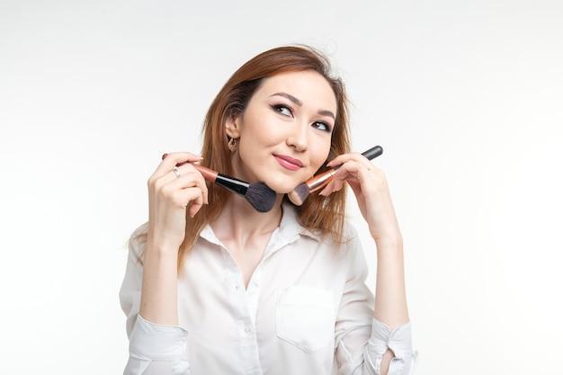Concepto de artista, belleza y personas de maquillaje - hermosa joven coreana sosteniendo pinceles de maquillaje en la pared blanca