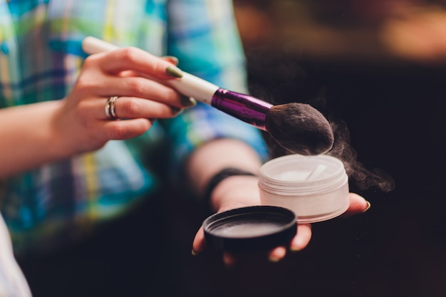 Concepto del artista de maquillaje, de la belleza y de la gente - mujer joven coreana hermosa que sostiene la paleta de sombras de ojos y de cepillos coloridos.