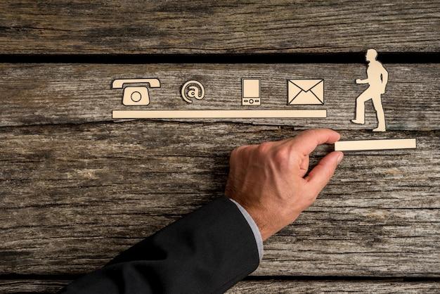 Concepto de asistencia con un empresario apoyando un corte de un hombre subiendo hacia una línea de iconos de contacto sobre un rústico