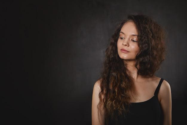 Concepto de astrología y misticismo. hermosa mujer joven con cabello largo voluminoso mirando hacia abajo y sonriendo misteriosamente