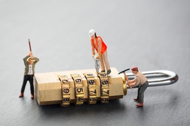 Concepto de ataque de piratería y problemas de seguridad. la gente en miniatura intenta desbloquear el candado de metal.