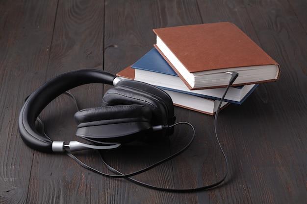 Concepto de audiolibro con auriculares y libro de papel sobre la mesa