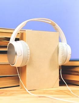 Concepto de audiolibro. libros sobre la mesa con auriculares puestos