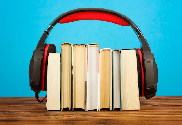 Concepto de audiolibros, pila de libros y auriculares