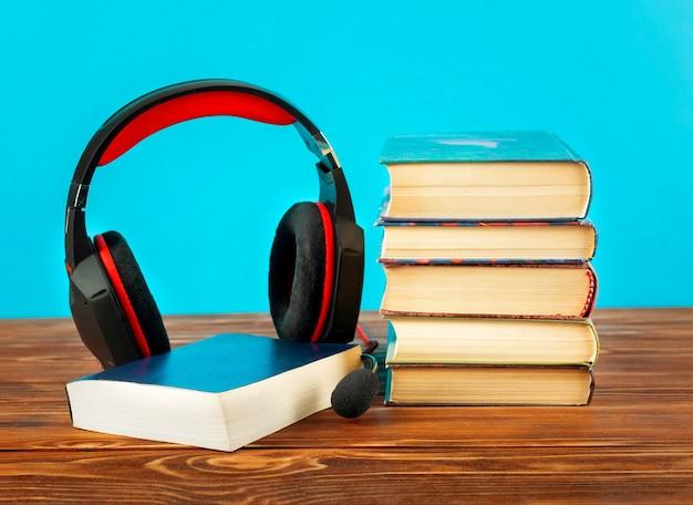 Concepto de audiolibros, pilas de libros y auriculares.