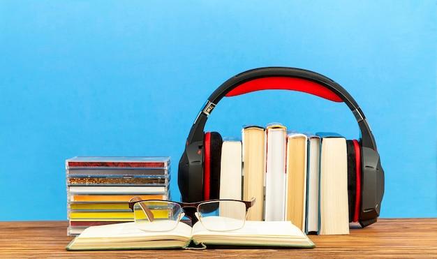 Concepto de audiolibros, pilas de libros, cd y auriculares.