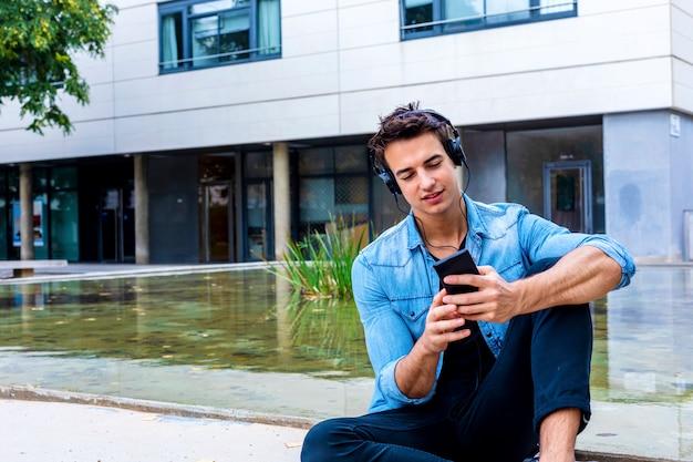 Concepto de los auriculares de la música que se sienta del hombre que escucha